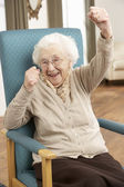 Senior Woman Celebrating In Chair At Home — Stock Photo