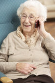 Senior Woman Talking On Mobile Phone Sitting In Chair At Home — Stock Photo