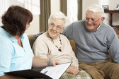 Senior Couple In Discussion With Health Visitor At Home — Foto de Stock