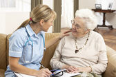 Senior Woman In Discussion With Health Visitor At Home — Stok fotoğraf