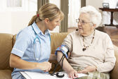Senior Woman Ihaving Blood Pressure Taken By Health Visitor At H — Fotografia Stock
