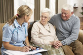 Senior Couple In Discussion With Health Visitor At Home — Fotografia Stock