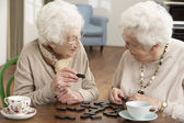 Due donne senior giocare domino al centro diurno — Foto Stock