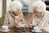 Zwei alte frauen, die an kindertagesstätte domino spielen — Stockfoto