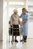 Carer Helping Elderly Senior Woman Using Walking Frame — Stock Photo
