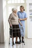 Carer Helping Elderly Senior Woman Using Walking Frame — Stock Photo