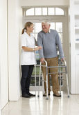 Carer Helping Elderly Senior Man Using Walking Frame — Stock Photo