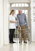 Carer Helping Elderly Senior Man Using Walking Frame — Stock Photo