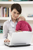 Woman With Newborn Baby Working From Home Using Laptop — Photo