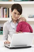 初生婴儿使用的便携式计算机的在家工作的女人 — 图库照片