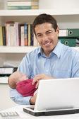 Ojciec z nowo narodzonego dziecka praca w domu przy użyciu laptopa — Zdjęcie stockowe