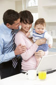 Parents With Baby Working From Home Using Laptop — Stock Photo