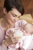 母亲喂养新生宝宝在家里的肖像 — 图库照片