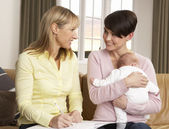 Mor med nyfött barn talar med hälsa besökare hemma — Stockfoto