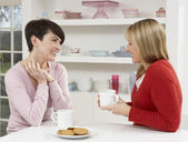 Two Women Enjoying Hot Drink In Kitchen — Stock Photo