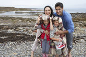 Family on beach with blankets — Stock Photo