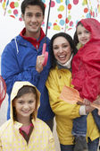 Happy family on beach with umbrella — Foto Stock