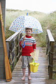 Boy standing on footbridge with umbrella — ストック写真
