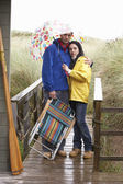 Young couple on beach with umbrella — Stok fotoğraf