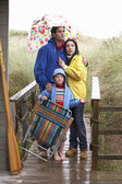 Family on beach with umbrella — Stock fotografie