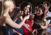 Young women drinking at bar — Stok fotoğraf