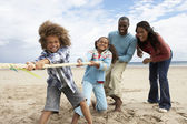 Family playing tug of war on beach — Stok fotoğraf