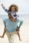 Father and son playing piggyback on beach — Stock Photo