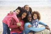 Young mixed race family embracing on beach — Stock Photo