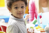 Boy playing with toys in nursery — Stok fotoğraf