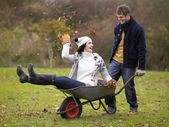 Young couple playing in wheelbarrow — Stockfoto