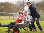 Two young couples playing in wheelbarrow — Stockfoto