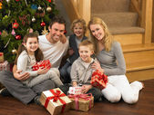 Family with gifts in front of Christmas tree — Stockfoto