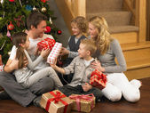 Family exchanging gifts in front of Christmas tree — Foto de Stock