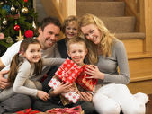 Family with gifts in front of Christmas tree — ストック写真