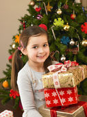 Young child holding gifts in front of Christmas tree — Stock fotografie