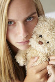 Unhappy teenage girl with cuddly toy — Stock Photo
