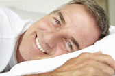Head and shoulders mid age man lying down — Stock Photo