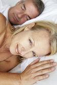 Meados de casal de idade, em mulher de cama acordado — Foto Stock