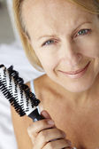 Mid age woman holding hairbrush — Stockfoto