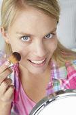 Teenage girl putting on make-up — Stock Photo
