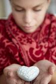 Tonårsflicka anläggning silver hjärta — Stockfoto