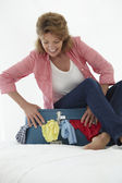 Senior woman struggling to close suitcase — Stock Photo