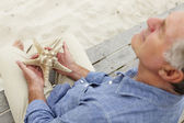 Senior man holding starfish — Stock Photo