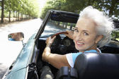 Senior woman in sports car — Foto Stock