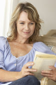 Mid age woman reading a book — Stock Photo