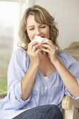 Mid age woman sneezing — Stock Photo