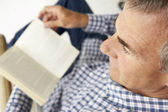 Mid age man reading a book — Stock Photo