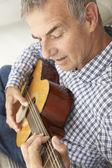 Połowie wieku człowiek gra gitara akustyczna — Zdjęcie stockowe