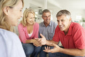 Mid age couples chatting at home — Stockfoto