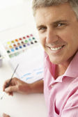 Mid age man painting with watercolors — Stock Photo